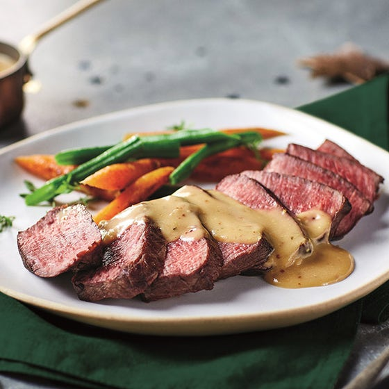 Béarnaise sauce on sliced steak on plate with vegetables
