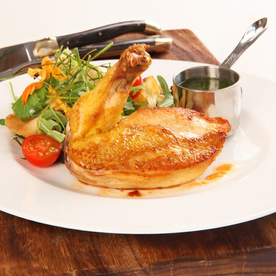 Corn-fed chicken supreme with salad on a white plate