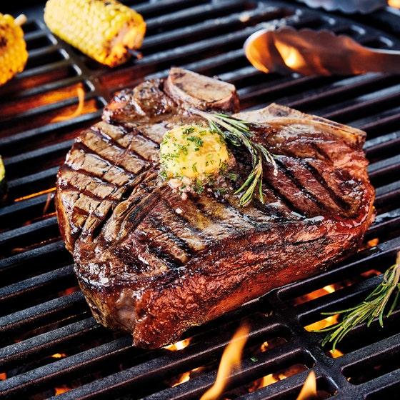 tarragon and black pepper butter on T-bone steak on barbeque